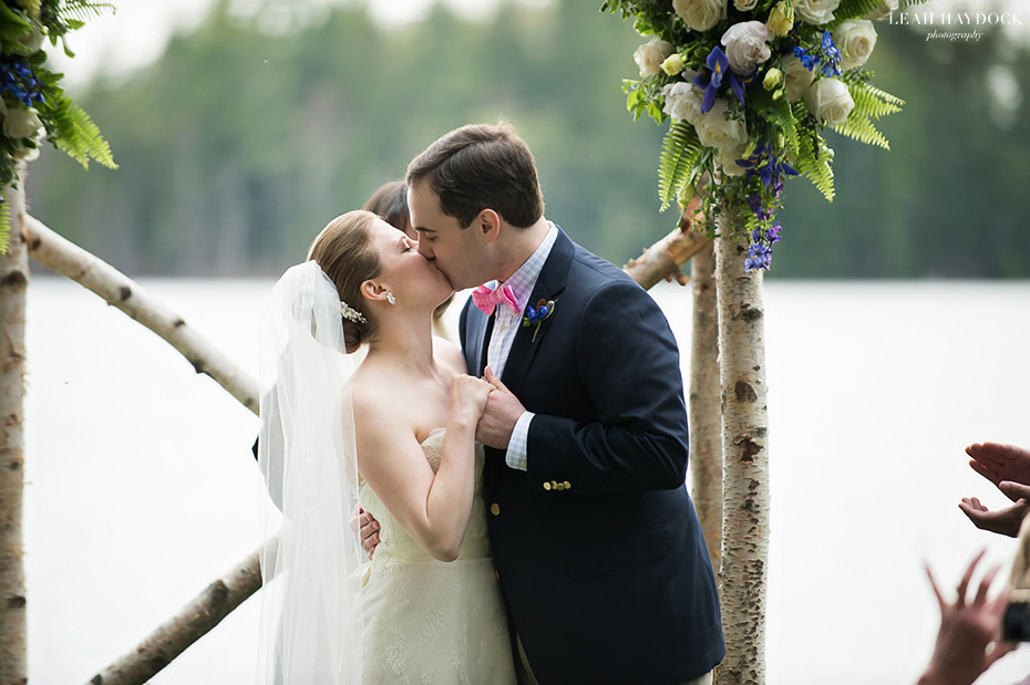 Newlyweds kissing at outdoor wedding ceremony at Migis Lodge in Maine