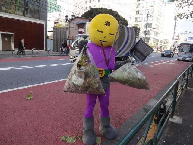 Mangetsu Man, super-héros nettoie une rue à Tokyo