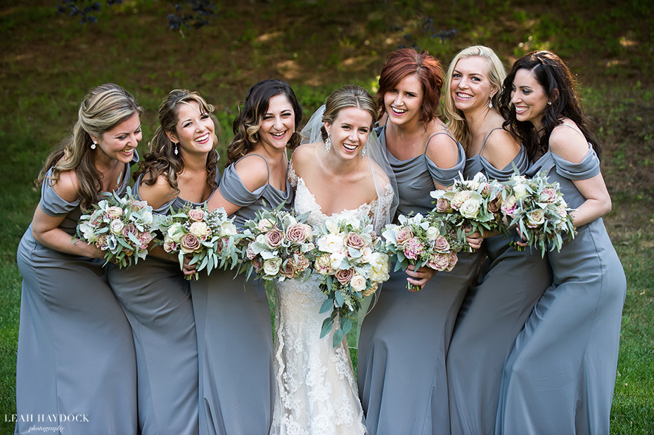 Giggling bridesmaids in soft gray dresses with muted flowers at a wedding at Glen Manor House
