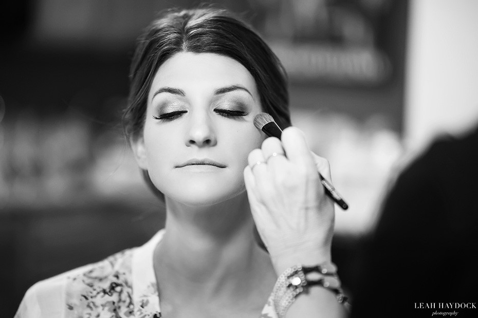 Black and white picture of bride having professional make up applied for her wedding