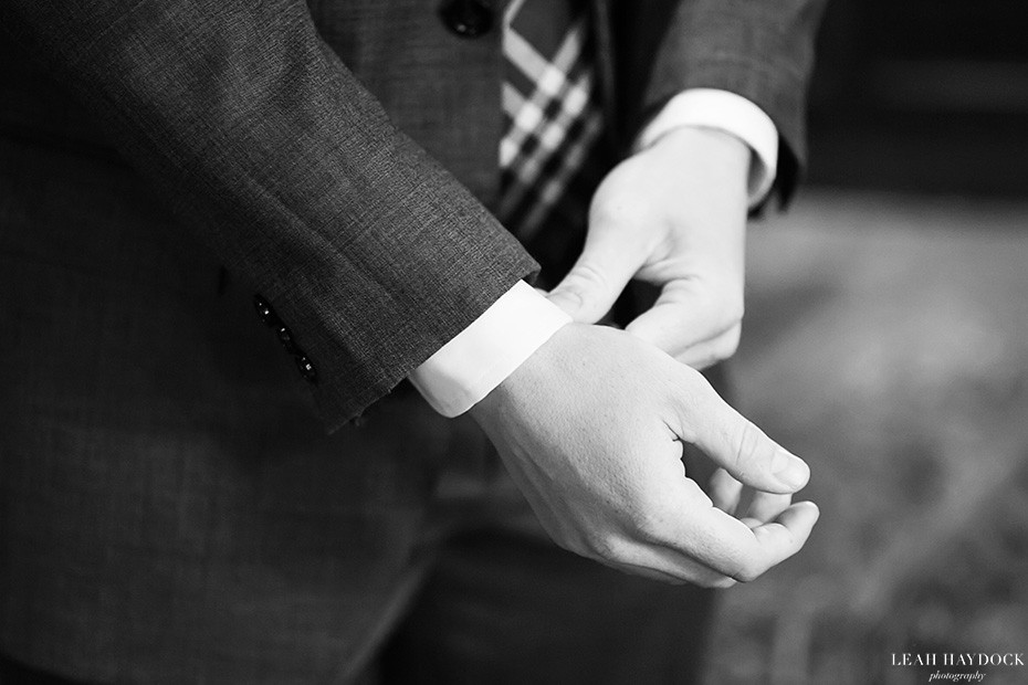 Black and white picture of groom adjusting his cufflinks before his wedding